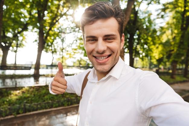 Feliz joven empresario vistiendo camiseta tomando un selfie mientras está de pie al aire libre en el parque de la ciudad, pulgares arriba