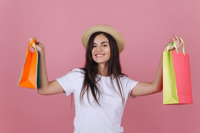 Feliz joven en un sombrero posa con coloridos bolsos de compras