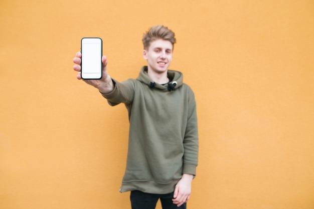 Feliz joven se encuentra en una pared naranja, muestra un teléfono inteligente con una pantalla en blanco