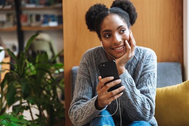 Feliz joven estudiante africana estudiando en la biblioteca, escuchando música con auriculares