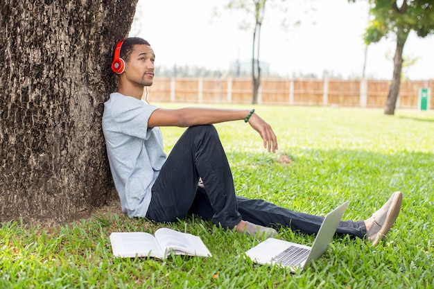 Feliz joven estudiante de escuchar música en el parque
