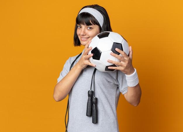 Feliz joven fitness chica con diadema con saltar la cuerda alrededor del cuello sosteniendo un balón de fútbol mirando a la cámara sonriendo alegremente parado sobre naranja