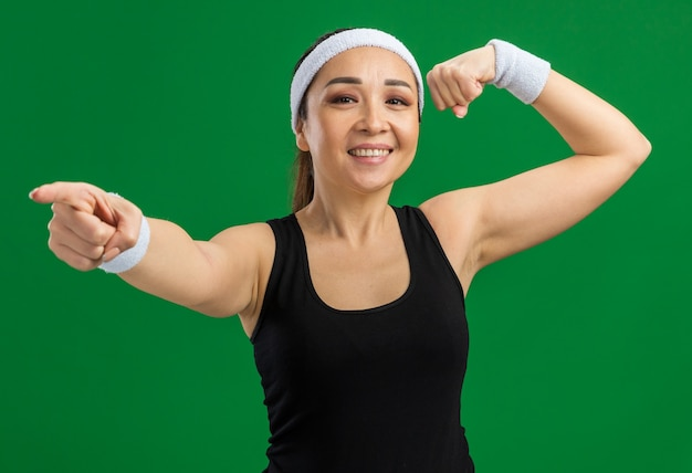 Feliz joven fitness mujer con diadema y brazaletes sonriendo confiado levantando puño mostrando bíceps