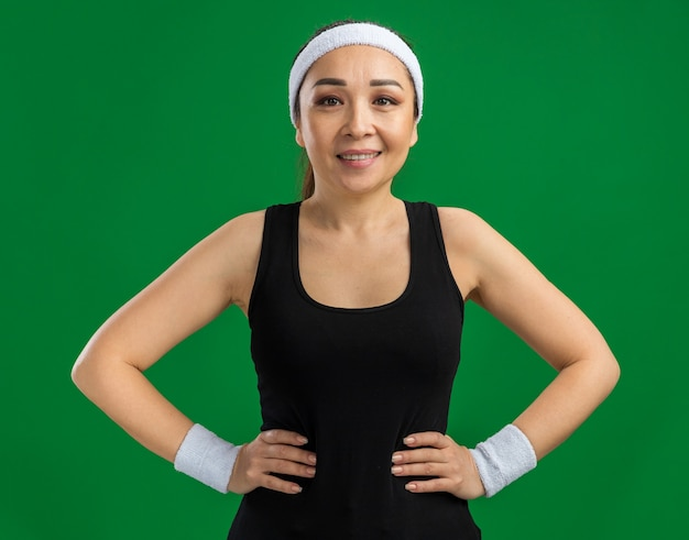 Feliz joven fitness mujer con diadema y brazaletes sonriendo confiados de pie sobre la pared verde