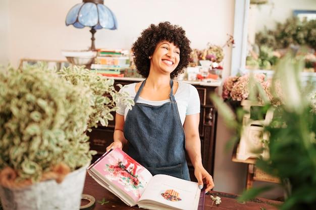Feliz joven florista femenina con álbum de fotos de flores en la tienda