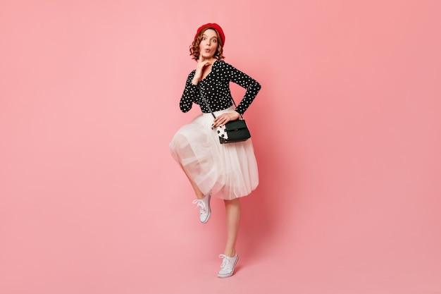 Feliz joven francés bailando con sonrisa. vista de longitud completa de la chica de moda en boina roja de pie sobre una pierna.