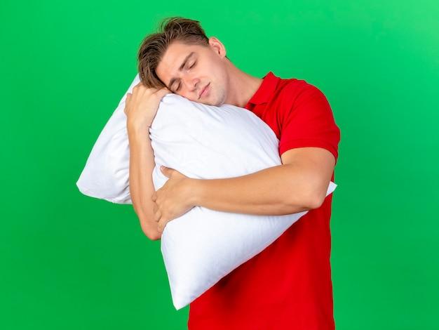 Feliz joven guapo rubio enfermo sosteniendo la almohada poniendo la cabeza sobre ella durmiendo aislado en la pared verde con copia sapce