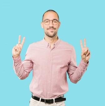Feliz joven haciendo un gesto de victoria con sus dedos