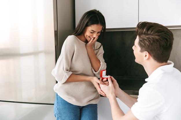 Feliz joven haciendo una propuesta a su novia con un anillo en una caja en casa