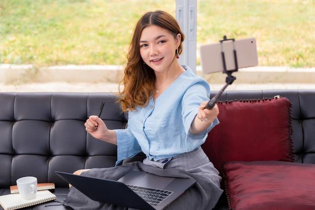 Feliz joven hermosa mujer asiática sosteniendo su teléfono en un palo selfie para tomar una foto o video de sí misma en su sala de estar