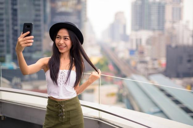 Feliz joven hermosa mujer turista asiática tomando selfie contra vista de la ciudad