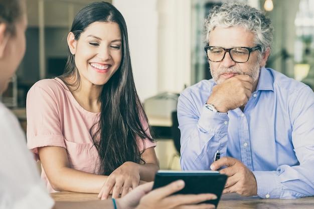 Feliz joven y hombre maduro reunidos con profesionales, viendo y discutiendo contenido en tableta
