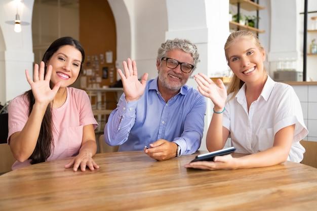 Feliz joven y hombre maduro, sentado a la mesa con mujeres profesionales con tableta, mirando a la cámara, posando, sonriendo y saludando
