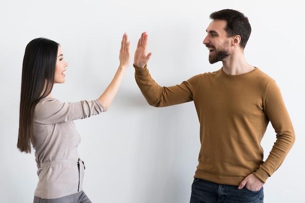 Feliz joven hombre y mujer choca esos cinco