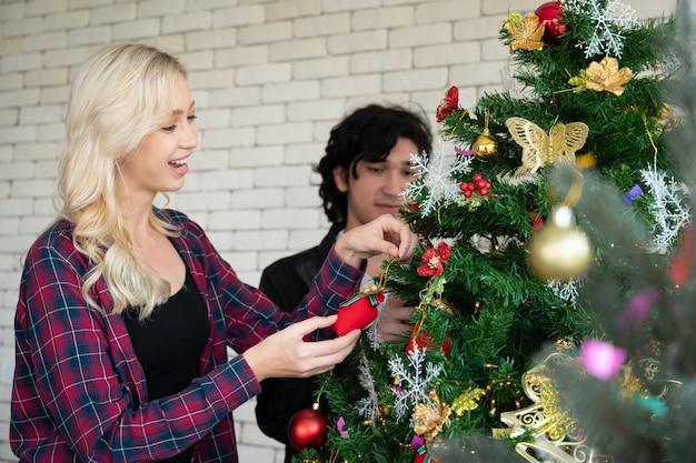 Feliz joven hombre y mujer en la fiesta de navidad, hermoso árbol y decoraciones.