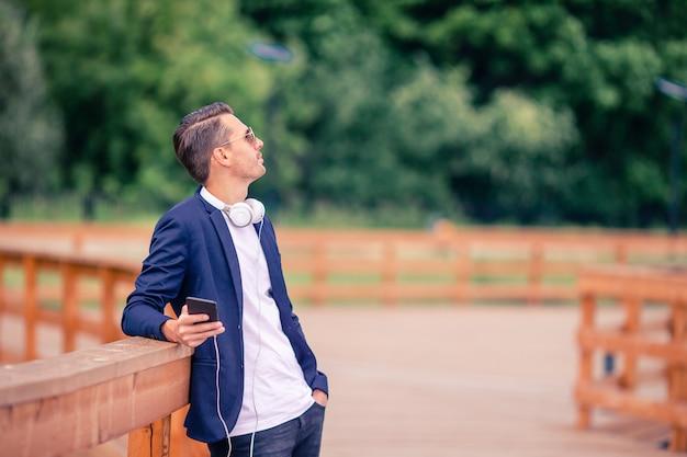 Feliz joven hombre urbano tomando café en la ciudad europea al aire libre