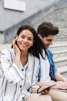 Feliz joven increíble pareja amorosa gente de negocios colegas al aire libre afuera en pasos usando teléfono móvil y computadora portátil escuchando música con auriculares.