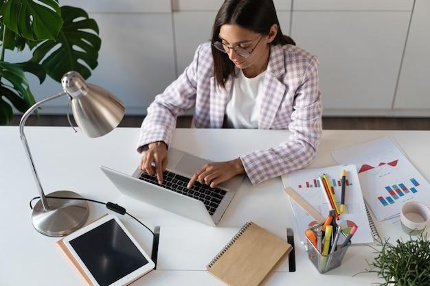Feliz joven indio mujer de negocios de raza mixta usando la computadora mirando la pantalla trabajando en internet sentarse en el escritorio de la oficina