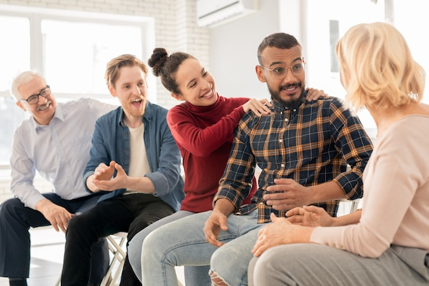 Feliz joven intercultural manteniendo sus manos sobre los hombros de su esposo o novio consultando con el psicólogo