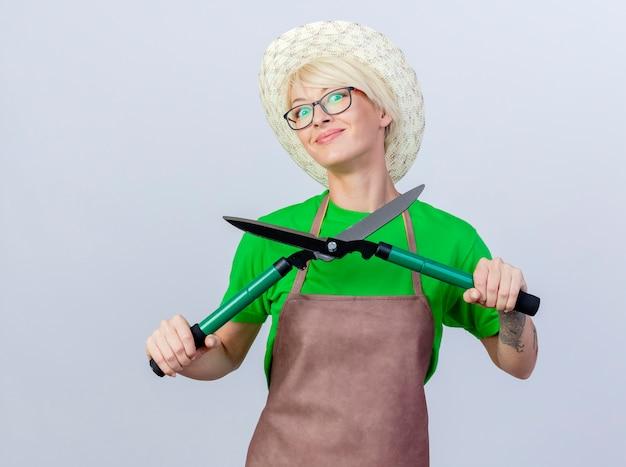 Feliz joven jardinero mujer con pelo corto en delantal y sombrero sosteniendo podadoras de setos sonriendo alegremente