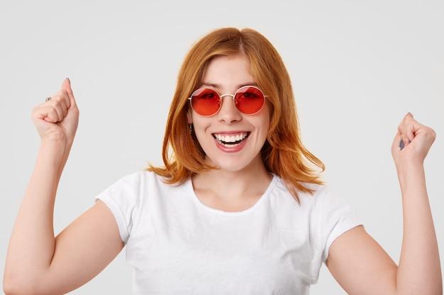 Feliz joven jengibre exitosa hembra mantiene los puños cerrados levantados, tiene una sonrisa de dientes, celebra el día exitoso