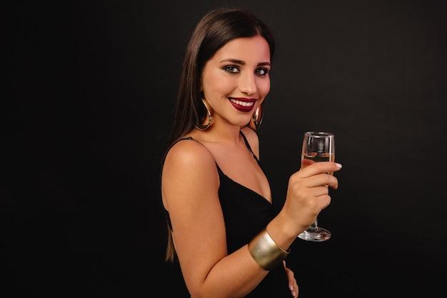 Feliz joven con joyas de oro en vestido negro bebiendo champán