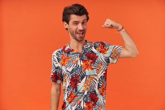 Feliz joven juguetón con rastrojo en camisa colorida guiñando un ojo y mostrando los músculos bíceps
