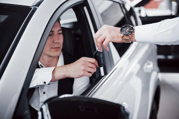 Feliz joven con llaves en las manos, suerte comprar un coche.