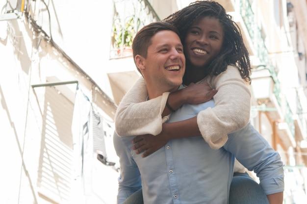 Feliz joven llevando novia en la espalda al aire libre