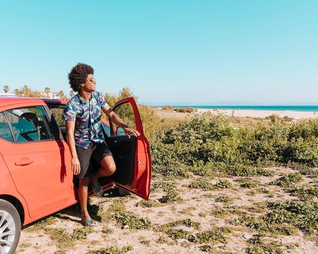 Feliz joven macho negro saliendo del coche en la playa