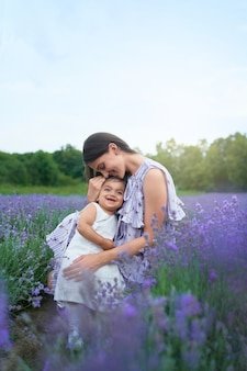 Feliz joven madre abrazando a un niño en el campo de lavanda