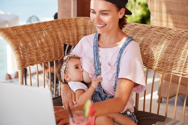 Feliz y joven madre amamanta a su pequeño hijo, lee un blog para mamás en internet, recibe consejos sobre cómo cuidar a los niños pequeños