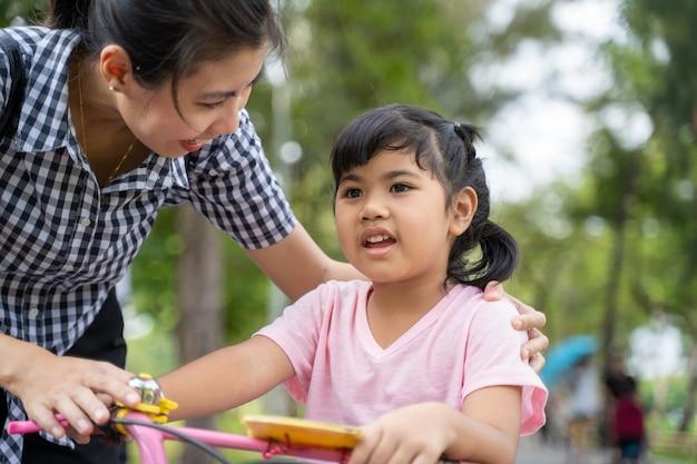 Feliz joven madre asiática y su hija hablando juntos en el parque