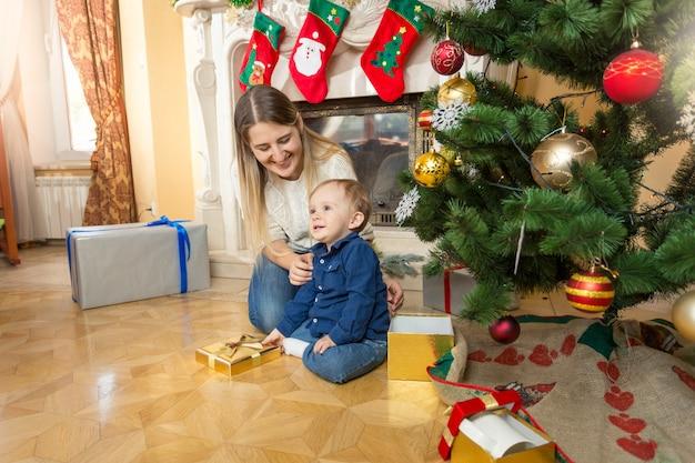 Feliz joven madre y un bebé de 1 año en el piso bajo el árbol de navidad en la sala de estar