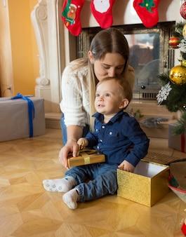 Feliz joven madre besando a su hijo en el árbol de navidad