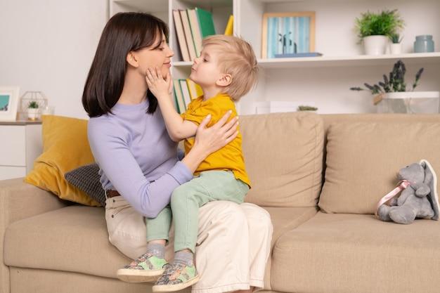 Feliz joven madre cariñosa y su pequeño y lindo hijo expresándose amor el uno al otro mientras están sentados en un sofá suave en la sala de estar en casa