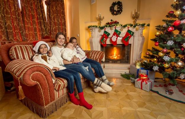 Feliz joven madre e hija sentada en el sofá junto a la chimenea en casa decorada para navidad