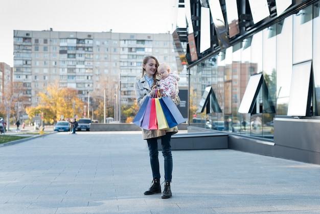 Feliz joven madre con hija pequeña en los brazos y bolsas de compras en la mano. dia de compras. centro comercial en la pared