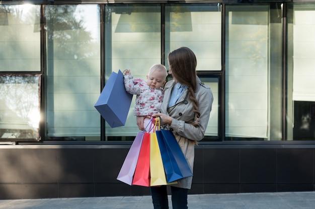 Feliz joven madre con hija pequeña en los brazos y bolsas de compras en la mano. dia de compras. centro comercial