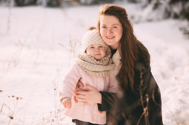 Feliz joven madre con hija a pie en el parque de invierno. de cerca. retrato familia feliz al aire libre.