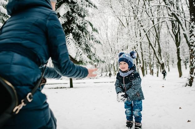 Feliz joven madre con hijo caminar en el parque de invierno. de cerca. retrato de familia feliz al aire libre.