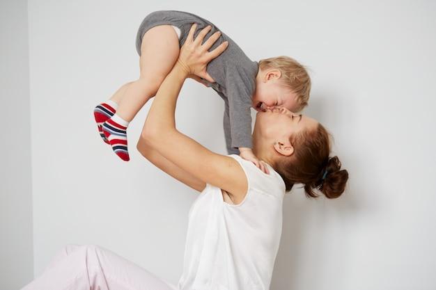 Feliz joven madre con hijo pequeño en casa
