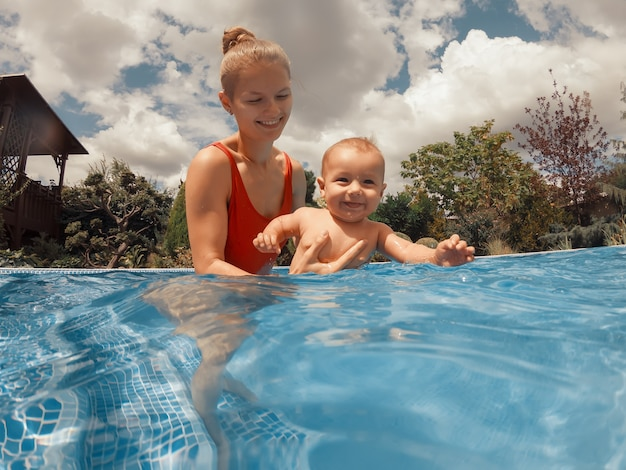 Feliz joven madre jugando con su bebé en la piscina al aire libre en un caluroso día de verano