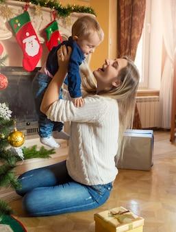 Feliz joven madre jugando con su bebé en el piso en el árbol de navidad