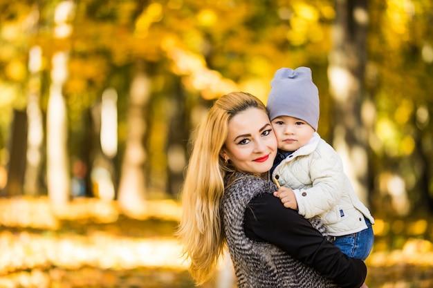 Feliz joven madre jugando con su pequeño hijo en otoño cálido sol o día de verano. hermosa luz del atardecer en el jardín de manzanas o en el parque. concepto de familia feliz