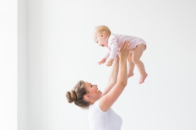 Feliz joven madre levantando lindo bebé en el aire, pasando y disfrutando el tiempo junto con su hija.