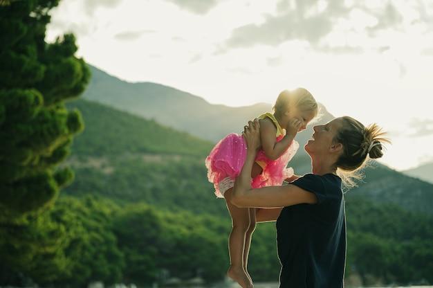 Feliz joven madre levantando a su hija pequeña en falda rosa en el aire por la mañana mientras el sol sale de las colinas de fondo.