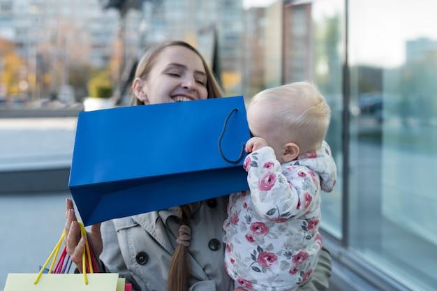 Feliz joven madre con una pequeña hija en brazos y divirtiéndose con bolsas. dia de compras. centro comercial en el fondo