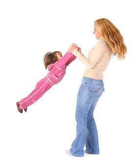 Feliz joven madre rubia sosteniendo y balanceando a su pequeña hija en ropa rosa en las manos sobre la pared blanca. concepto de estilo de vida de niños felices hermosos