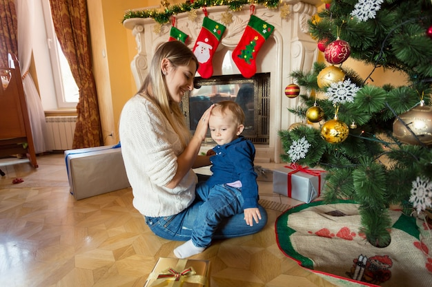 Feliz joven madre sentada con su bebé en el suelo en el árbol de navidad